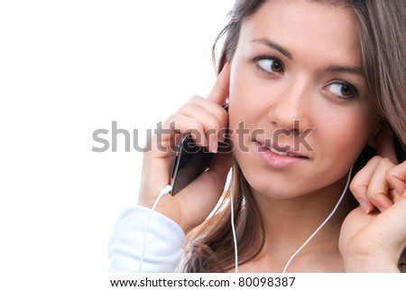 Close-up portrait of young girl listening, enjoying music and holding cellular and talking on mobile phone in earphones isolated on white background