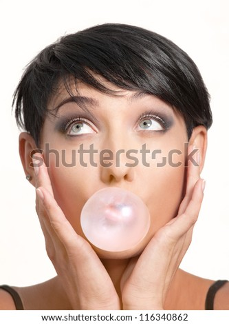 Close-up portrait of young girl with pink chewing gum on white background