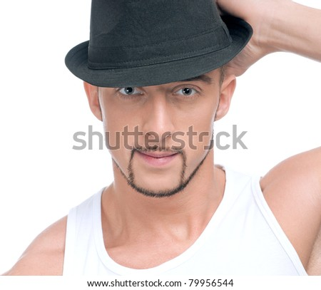 Close up portrait of young handsome man with perfect skin and hair. In black hat
