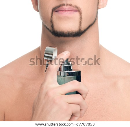 Close up portrait of young handsome man with perfect skin applying perfume. Isolated on white