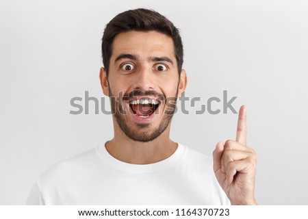 Close up portrait of young handsome smiling man with mouth wide open, in white t-shirt, having great innovative idea, pointing his finger in eureka sign