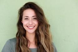 Close up portrait of young happy woman on green background