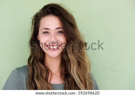 Close up portrait of young happy woman on green background #592698620