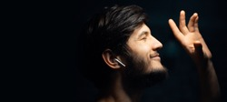 Close-up portrait of young hipster man, listen the music with wireless earphones, on black background.