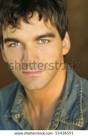 Close-up portrait of young man in denim shirt against brown background
