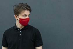 Close-up portrait of young man walking in black t-shirt and red medical mask on dark gray background for protect and stop viruses and coronavirus pandemic, covid-19 outbreak. Guy in red mask