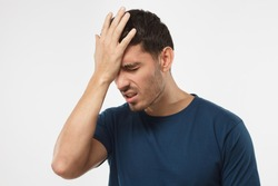 Close up portrait of young man with face palm gesture. Disappointed stressed out male in blue t-shirt making facepalm with hand.