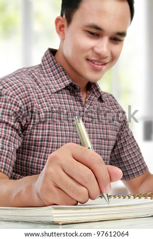 close up portrait of young man writing on notebook