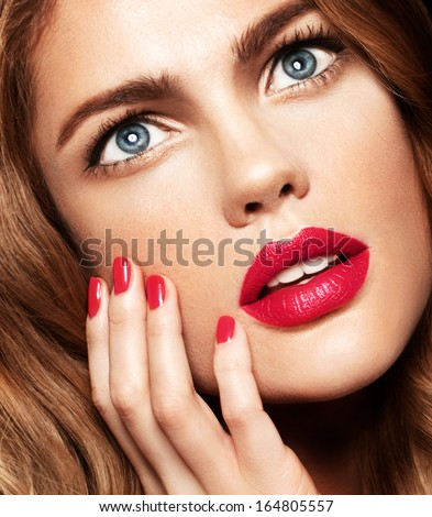 close up portrait of young model with red lips and red manicure blue eyes, perfect skin