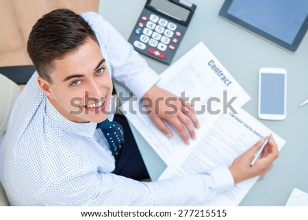 Close up portrait of young office worker at desk.Top view of young man at table with pen and documents.