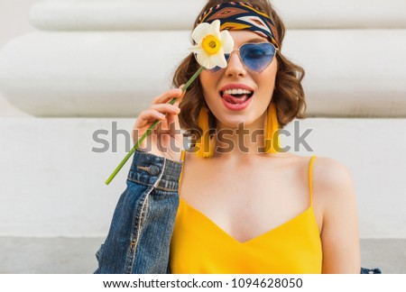 close-up portrait of young pretty woman with funny face expression, emotional, wearing stylish hippie apparel, denim jacket, yellow top, holding flower, sunny summer, sunglasses, hippie style