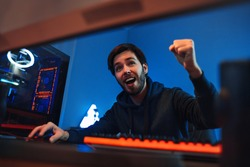 Close up portrait of young pro gamer is happy with winning online video game, shows YES hand gesture, smiling. Exited male cyber sportsman won the tournament and celebrating the victory. Cyber sport