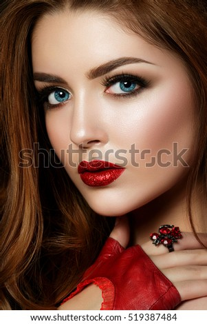 Stock Photo Close up portrait of young red-haired woman wearing red lips with glitters and brown smokey eyes. Perfect eyebrows. Modern fashion make up. Studio shot
