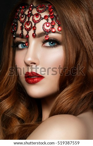 Stock Photo Close up portrait of young red-haired woman wearing red lips with glitters and brown smokey eyes. Modern fashion make up. Studio shot