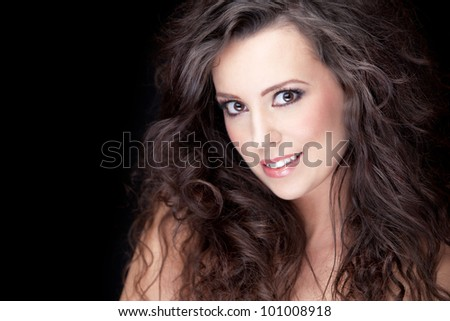close-up portrait of young smiling brunette with long curly hair, shallow DOF, clear focus on model's eye
