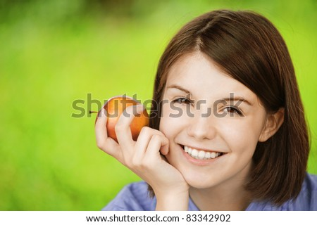 Close-up portrait of young smiling brunette woman holding red apple at summer green park.