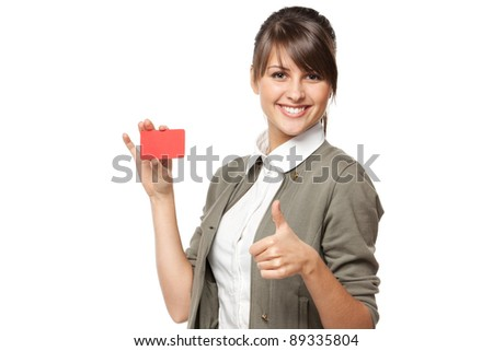 Close-up portrait of young smiling business woman holding credit card and showing thumb up sign isolated on white background