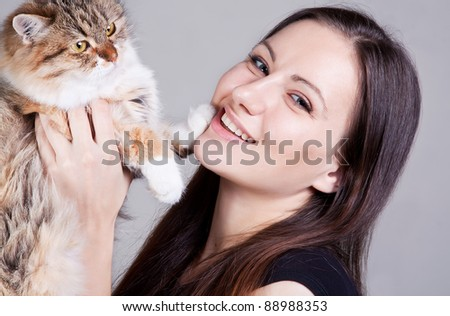 Close-up portrait of young smiling woman with cat in hands