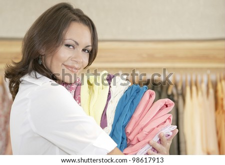 Close up portrait of young store attendant holding a pile of clothes in a fashion store.