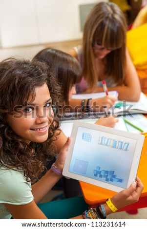 Close up portrait of young student at desk showing  homework on digital tablet.
