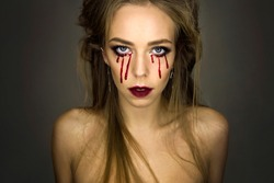 Close-up portrait of young stylish sexy blonde girl with dark bloody makeup with blood drops from eyes which is standing and looking straight on gray background, halloween concept, free space