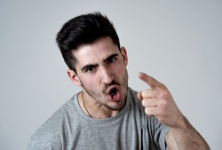 Close up portrait of young violent man with angry face looking furious and crazy showing fits and pointing finger at the camera. Human facial expressions, emotions and behavioral problems concept.