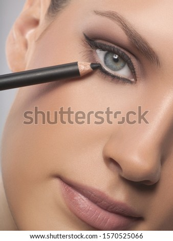 Close-up portrait of young woman applying eyeliner, studio shot