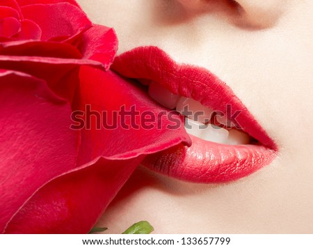 close-up portrait of young woman biting red rose's petal