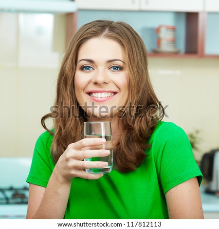Close up portrait of Young Woman drinking water at home interior. Clothes of green color.