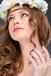 close-up portrait of young woman in floral wreath spraying perfume isolated on grey