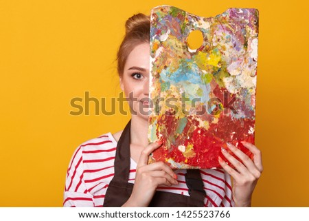 Close up portrait of young woman painter against yellow studio wall, draws picture, lady wearing casual striped shirt and brown apron, girl artist covers half of her face with palette of colours.