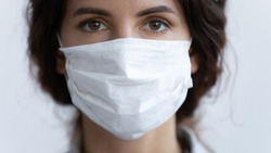 Close up portrait of young woman wear medical mask protecting from coronavirus pandemic, serious millennial female in protective face cover against spread of covid-19 virus, corona, epidemic concept