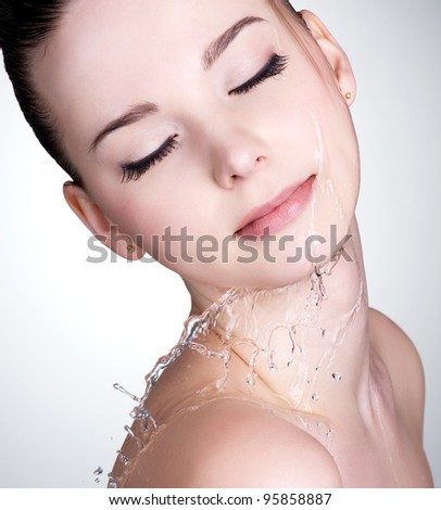 Close-up portrait of young woman with drops of water on her beautiful face