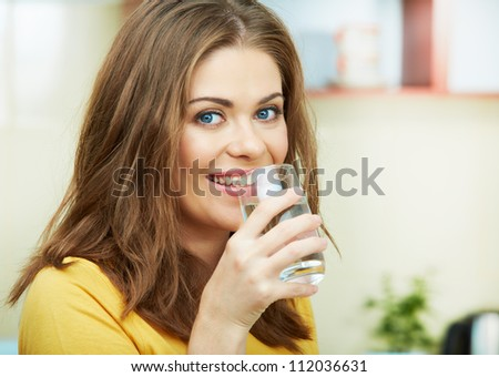 Close up portrait of Young Woman with water glass standing against  home kitchen interior.