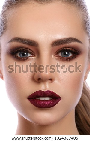 Stock Photo Close up portrait of young woman with wine red lips and bronze smokey eyes. Modern fashion make up. Studio shot