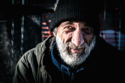 Close up portrait old smiling homeless alcoholic man face with white beard and hair wandering on the street depressed sick and lonely on cold winter day social issues homelessness documentary concept