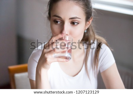 Close up portrait pensive serious millennial woman holding glass drink still water. Beautiful healthy pensive female on diet starting day with fresh natural water healthy lifestyle good habit concept