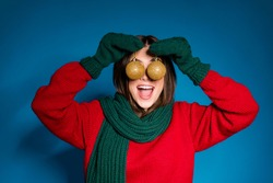 Close up portrait photo of cute playful young girl open mouth hold two baubles hiding eyes funny decorating house wear red pullover green scarf gloves isolated dark blue color background