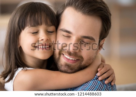Close up portrait pretty mixed race daughter embracing Caucasian father sitting on couch at home. Multi-ethnic people with closed eyes enjoy spend time together. Happy diverse multiracial family con