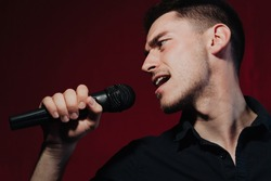 Close up portrait Rock band vocalist singing to microphone in lights on red background