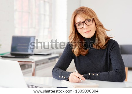Close-up portrait shot of middle aged businesswoman wearing casual clothes while sitting at office desk and doing some paperwork. #1305090304