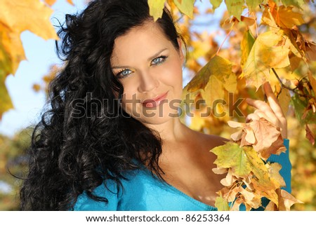 Close up Portrait smiling woman in autumn leaves outdoors