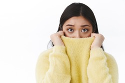 Close-up portrait timid and insecure cute asian girl pull sweater collar on face as feel afraid and scared of horror movie, eyes exress fear, trembling frightened, standing white background