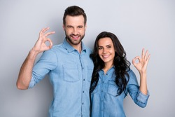 Close up portrait two amazing she her he him his couple lady guy couple stand close hold hands arms show okey symbol wear casual jeans denim shirts outfit clothes isolated light grey background