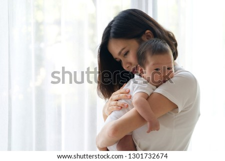 Close up portrait view of beautiful Asian mother holding her newborn baby in her arms and support baby's back by her hand with white curtain in background. She is feeling happy to stay with her child.