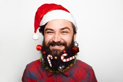 Close up portrait Young Man with Santa Hat and decorated beard smiling over white background
