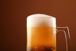 Close up pouring lager beer with white froth and bubbles in glass mug over dark brown background with copy space, low angle side view