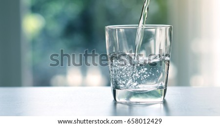 Photo of  Close up pouring purified fresh drink water from the bottle on table in living room