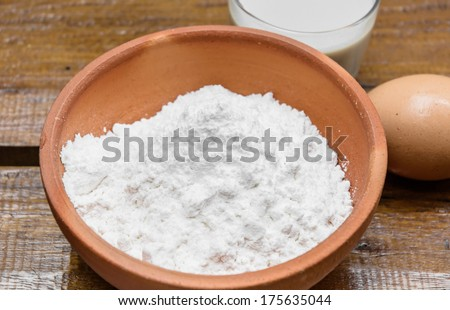 close up powder and milk with eeg for make bakery on wood table