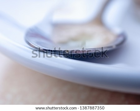 close-up precisely placed spot on the edge of a small silver-colored spoon, he lies on a white plate, around soft, soft background. #1387887350